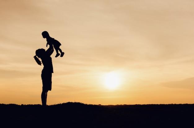 Silueta De Madre E Hija Levantando Al Niño En El Aire Sobre El Cielo