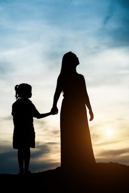 Silueta de la madre con su hija de pie y puesta de sol Foto gratis