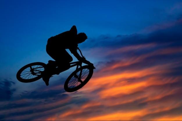 Silueta de un motorista saltando contra el hermoso cielo al atardecer Foto Premium