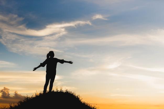 Silueta de mujer celebrando el éxito en la cima de una colina en la ...