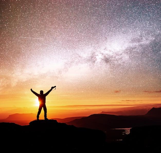 La silueta de la mujer está de pie en la cima de la montaña y apunta a la vía láctea antes del amanecer y disfruta con el colorido cielo nocturno Foto gratis