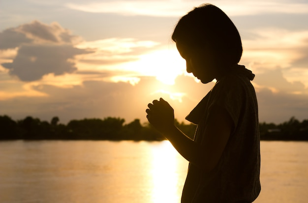 Silueta de mujer rezando sobre fondo hermoso atardecer. | Foto Premium