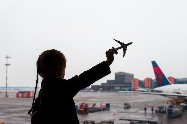 Silueta negra de un pequeño modelo de avión de juguete en el aeropuerto en manos de los niños Foto Premium