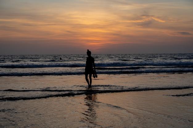 Silueta de una niña caminando sobre el agua en una playa con sus zapatos en la mano mientras se pone el sol Foto gratis