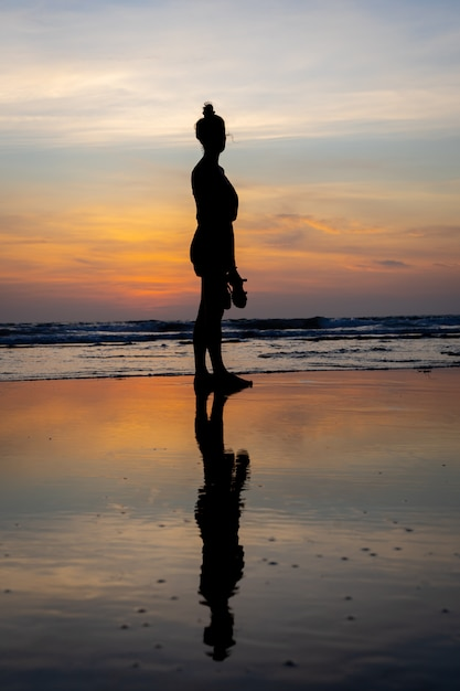 Silueta de una niña de pie en el agua en una playa Foto gratis