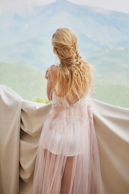 Silueta de la novia hermosa de la muchacha en los soportes de un peignoir del balcón que pasa por alto las montañas Foto Premium