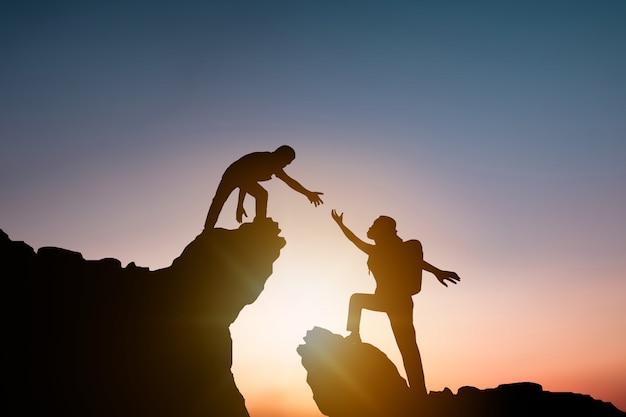 Silueta personas ayudando a otro excursionista escalada roca y montaña Foto Premium