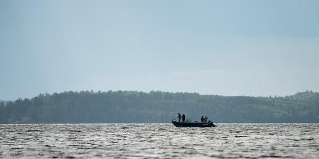 Silueta de personas en barco en un lago, lago de los bosques, ontario, canadá