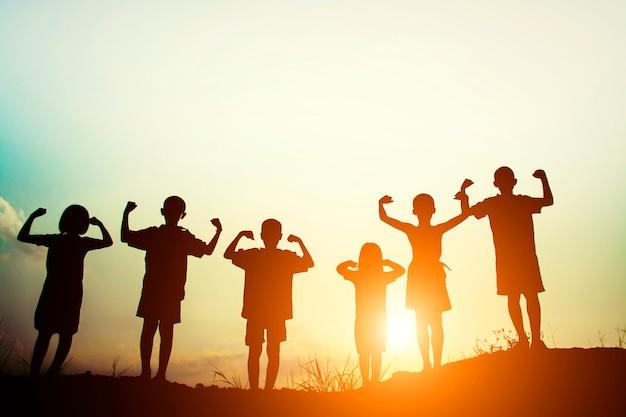 Siluetas de niños mostrando músculos al atardecer Foto Gratis