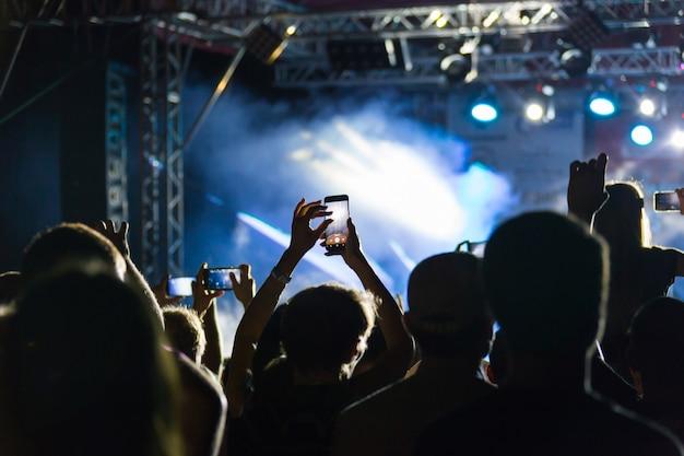 Siluetas de multitud en concierto cerca del escenario Foto Premium