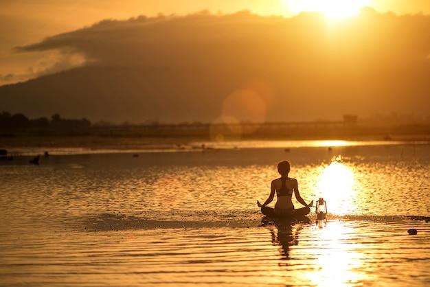 Siluetee a la mujer joven que practica yoga en la playa en la puesta del sol. Foto Premium