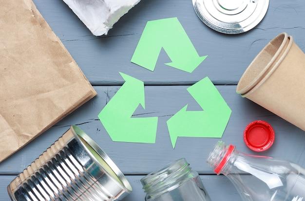 Un símbolo de reciclaje de basura verde y plástico, basura de hierro en un gris Foto Premium