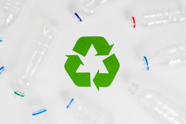 Símbolo de reciclaje ecológico verde y botellas de plástico. Foto gratis