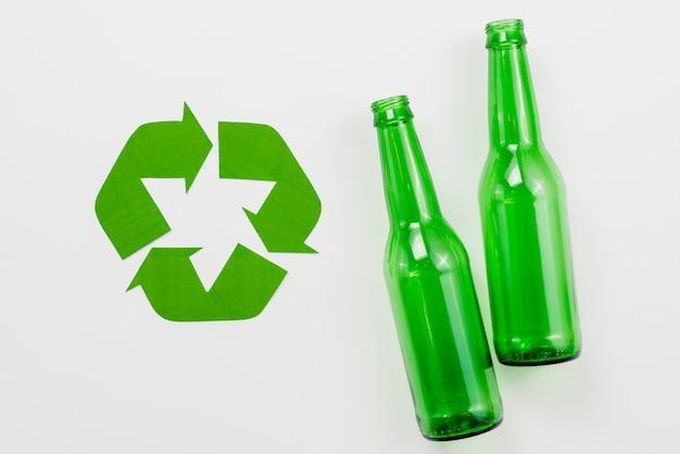 Símbolo de reciclaje junto a botellas de vidrio. Foto gratis