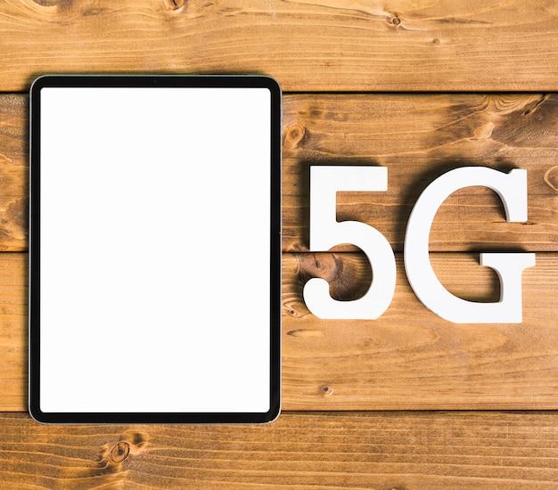Símbolos 5g y tableta en escritorio de madera Foto gratis