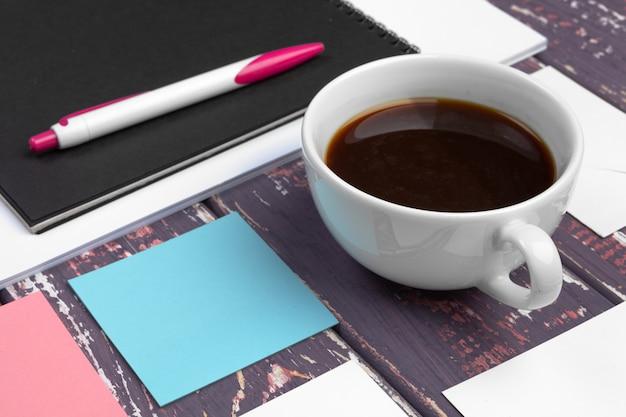 Simulacros de conjunto de plantilla de identificación, cuaderno y taza de café. descanso Foto Premium