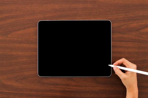 Simulacros de dispositivo de tableta digital con lápiz digital en mano sobre fondo de madera. Foto Premium