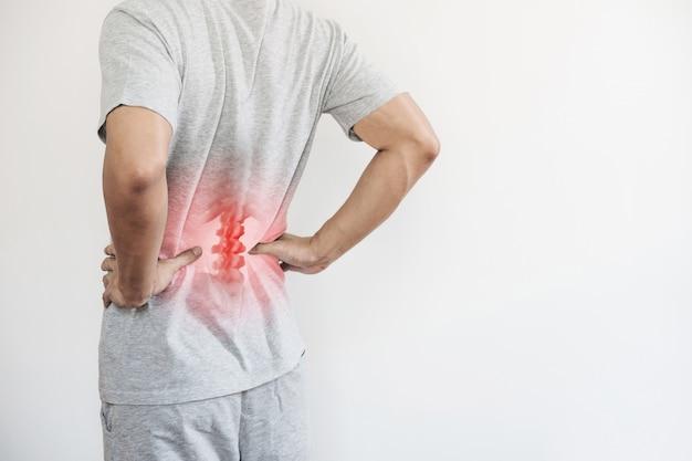 Síndrome de office, dolor de espalda y lumbalgia. un hombre tocando su espalda baja en el punto de dolor Foto Premium