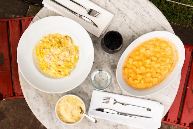 Sirva platos de pasta italiana en una mesa de mármol en el restaurante. Foto gratis