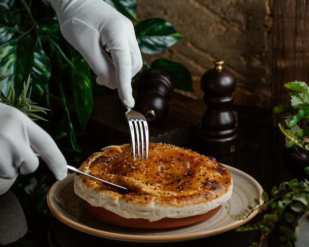 Un sirviente cortando cuidadosamente el pastel de carne dentro de un plato de cerámica Foto gratis