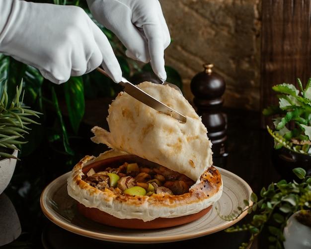 Un sirviente cortando la parte superior del pastel de carne dentro de una vasija de cerámica Foto gratis