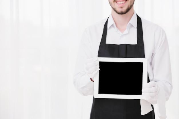 Sirviente sonriente sosteniendo una tableta con maqueta Foto Premium