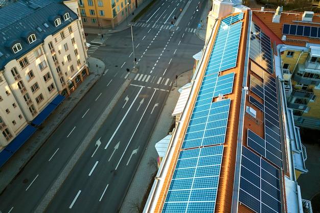 Sistema de paneles fotovoltaicos solares azules en la parte superior del techo del edificio de apartamentos en un día soleado Foto Premium