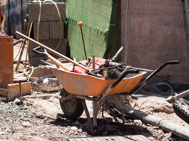 Sitio de construcción con carretilla llena de herramientas Foto gratis