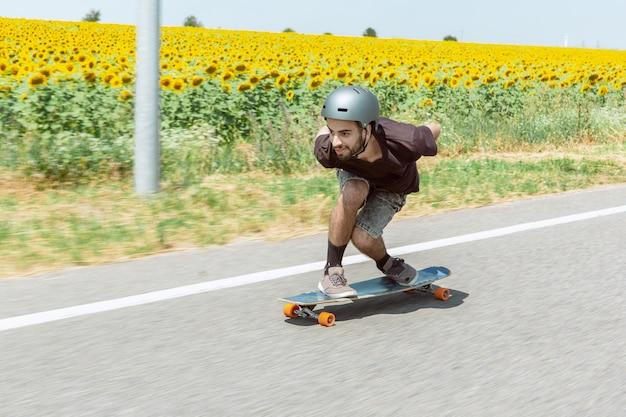 Skater haciendo un truco en la calle de la ciudad en un día soleado. joven en equipo de equitación y longboard en acción. concepto de actividad de ocio, deporte, extremo, afición y movimiento. tan rápido como un coche. Foto gratis
