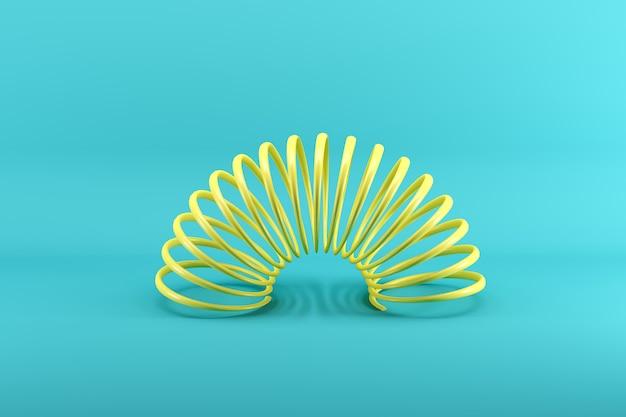 Slinky amarillo aislado en azul Foto Premium