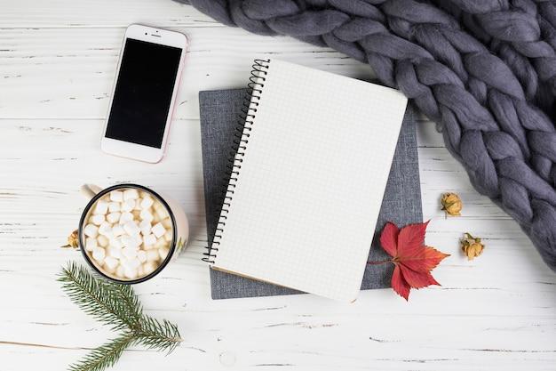 Smartphone cerca de rama de abeto, taza con malvaviscos y cuaderno Foto gratis
