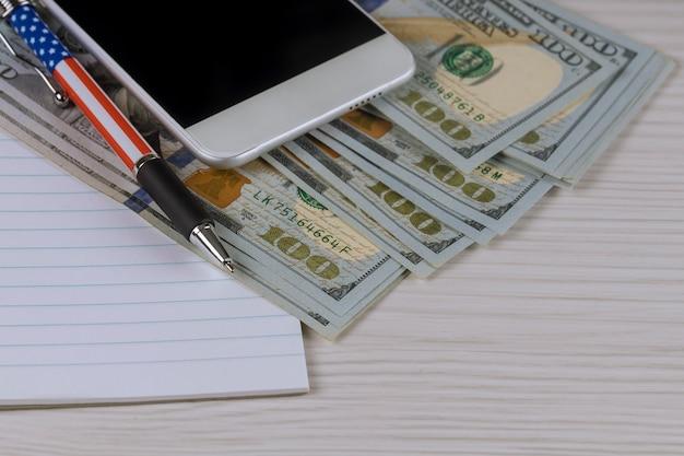 Smartphone, un cuaderno y una pluma en billetes de cien dólares. Foto Premium