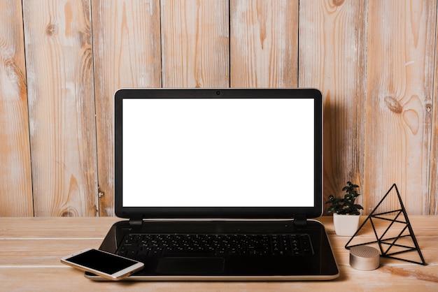 Smartphone en laptop con pantalla blanca en blanco en escritorio de madera Foto gratis