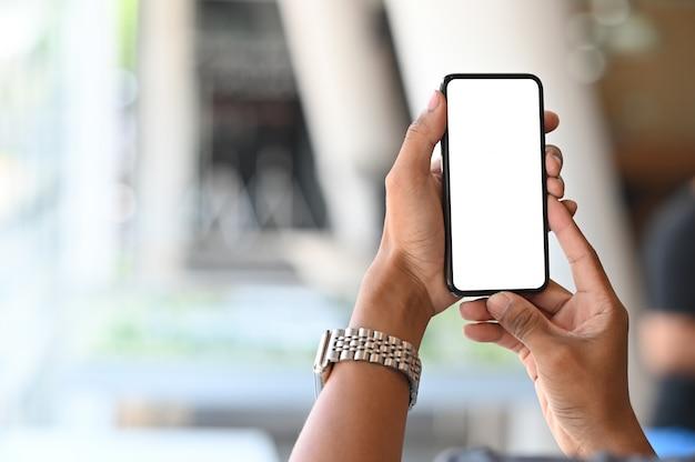 Smartphone en manos del hombre con pantalla vacía y bokeh en sala de desenfoque Foto Premium