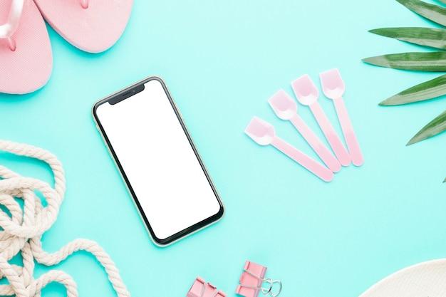 Smartphone con objetos marinos sobre fondo claro Foto gratis