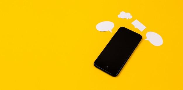 Smartphones con burbujas de discurso de papel sobre fondo amarillo. concepto de comunicación. vista superior. copia espacio composición de papel Foto Premium