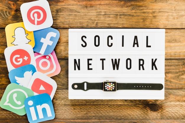 Smartwatch con iconos de redes sociales sobre la mesa de madera Foto gratis