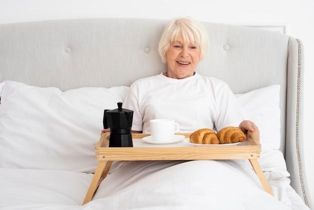 Smiley anciana con bandeja en el dormitorio Foto gratis