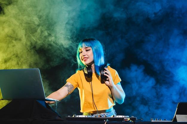 Smiley dj femenino controlando la atmósfera Foto gratis
