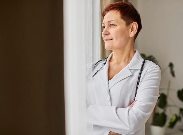 Smiley elder covid recovery center doctora mirando por la ventana Foto gratis