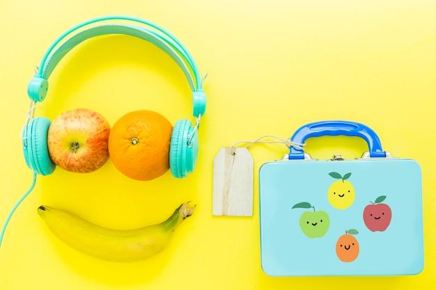 Smiley de frutas cerca de la lonchera Foto gratis