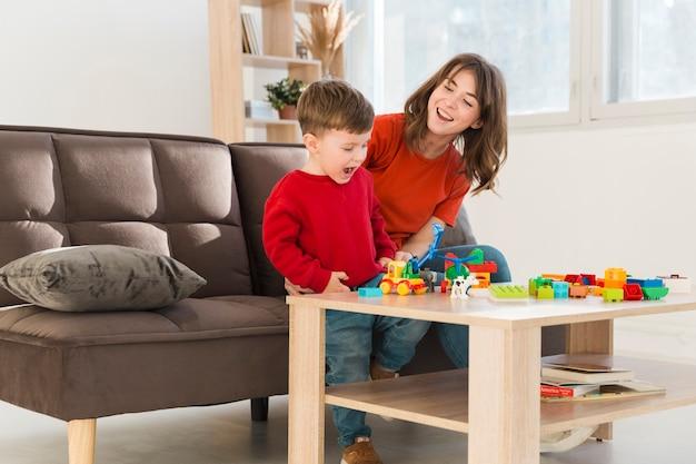 Smiley madre viendo hijo jugando Foto gratis