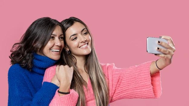 Smiley mamá e hija tomando selfie Foto gratis
