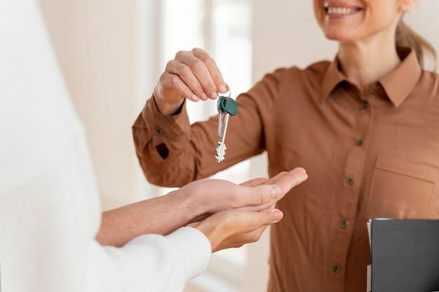 Smiley mujer agente de bienes raíces entregando a pareja las llaves de su nuevo hogar Foto gratis