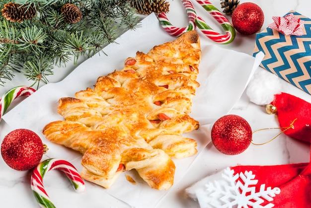 Snacks para la fiesta de navidad. pizza cerrada de hojaldre en forma de árbol de navidad. sobre una mesa de mármol blanco. con decoraciones navideñas Foto Premium