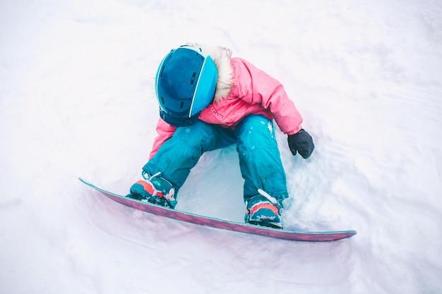 Snowboard deporte de invierno. niña niño jugando con nieve con ropa de invierno cálido. invierno Foto Premium
