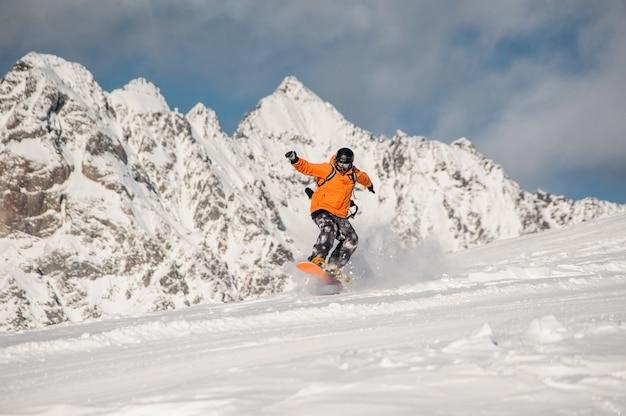 Snowboarder activo montando en la ladera de la montaña Foto Premium