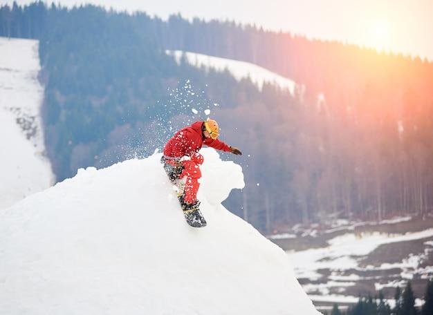Snowboarder masculino cabalgando desde la cima de la colina nevada con snowboard en la estación de esquí de invierno Foto Premium