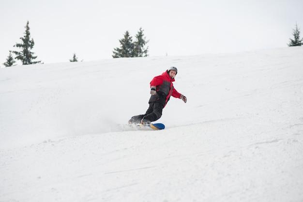 Snowboarder masculino cabalgando sobre la pendiente en la ladera nevada Foto Premium