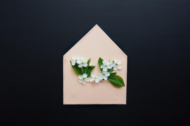 Sobre abierto con arreglos florales de primavera sobre fondo negro Foto Premium